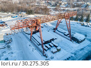 Купить «Open warehouse for storage of large diameter metal pipes. A gantry crane is installed in the territory. Winter sunny day.», фото № 30275305, снято 23 января 2019 г. (c) Андрей Радченко / Фотобанк Лори