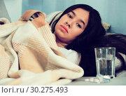 Купить «Sick and sad young female lying at sofa», фото № 30275493, снято 30 мая 2017 г. (c) Яков Филимонов / Фотобанк Лори