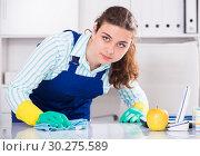 Купить «Female office cleaner is cleaning dust from the desk», фото № 30275589, снято 21 мая 2017 г. (c) Яков Филимонов / Фотобанк Лори