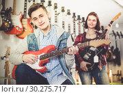 Купить «Female and male rock-n-roll players are deciding on suitable amp», фото № 30275717, снято 14 февраля 2017 г. (c) Яков Филимонов / Фотобанк Лори
