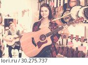 Купить «teenage customers deciding on suitable acoustic guitar in guitar shop», фото № 30275737, снято 14 февраля 2017 г. (c) Яков Филимонов / Фотобанк Лори