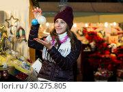 Купить «Woman choosing Christmas decoration at market», фото № 30275805, снято 22 декабря 2016 г. (c) Яков Филимонов / Фотобанк Лори