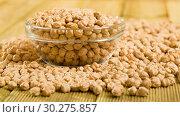 Купить «Glass jar with boiled chickpeas and bowl of raw chickpea grains on wooden surface», фото № 30275857, снято 7 декабря 2019 г. (c) Яков Филимонов / Фотобанк Лори