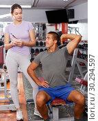 Купить «Man and girl capturing on paper training results», фото № 30294597, снято 15 октября 2018 г. (c) Яков Филимонов / Фотобанк Лори
