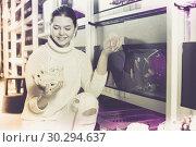 Купить «Girl at aquarium store choosing interesting stones, rocks and corals», фото № 30294637, снято 17 февраля 2017 г. (c) Яков Филимонов / Фотобанк Лори
