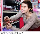 Купить «Smiling woman customer browsing rows of lipstick», фото № 30294677, снято 21 февраля 2017 г. (c) Яков Филимонов / Фотобанк Лори