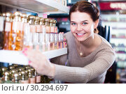 Купить «cheerful woman customer deciding on perfume variants in cosmetics shop», фото № 30294697, снято 21 февраля 2017 г. (c) Яков Филимонов / Фотобанк Лори