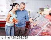 Купить «Positive couple customers choosing meat in shop», фото № 30294789, снято 22 июня 2018 г. (c) Яков Филимонов / Фотобанк Лори