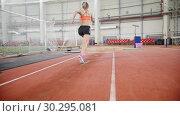 Купить «Young woman running and performing a long jump in the sports arena», видеоролик № 30295081, снято 26 марта 2019 г. (c) Константин Шишкин / Фотобанк Лори