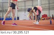 Купить «Two young athletic women warming up before training», видеоролик № 30295121, снято 21 марта 2019 г. (c) Константин Шишкин / Фотобанк Лори