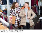 Купить «Woman trying new coat in showroom», фото № 30299897, снято 6 декабря 2018 г. (c) Яков Филимонов / Фотобанк Лори