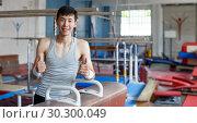 Купить «Positive young man asian acrobat posing at modern sport gym», фото № 30300049, снято 18 июля 2018 г. (c) Яков Филимонов / Фотобанк Лори