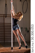Купить «Young woman in denim shorts practicing pole dancing», фото № 30300053, снято 22 апреля 2019 г. (c) Яков Филимонов / Фотобанк Лори