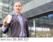 Купить «Professional woman with coffee outdoors», фото № 30300121, снято 6 мая 2017 г. (c) Яков Филимонов / Фотобанк Лори