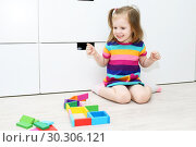 Little girl playing with educational toy at home on the floor. Стоковое фото, фотограф ivolodina / Фотобанк Лори
