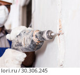 Купить «Professional constructor in helmet is perforating wall with drill», фото № 30306245, снято 18 мая 2017 г. (c) Яков Филимонов / Фотобанк Лори