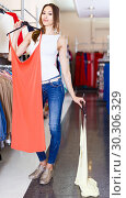 Купить «Portrait of young woman choosing new dress in boutique», фото № 30306329, снято 11 апреля 2017 г. (c) Яков Филимонов / Фотобанк Лори