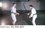 Купить «Two men in kimono training kendo on a parking lot», видеоролик № 30306861, снято 8 июля 2020 г. (c) Константин Шишкин / Фотобанк Лори