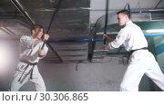 Купить «Two men in kimono training kendo on a parking lot. Sword fight», видеоролик № 30306865, снято 8 июля 2020 г. (c) Константин Шишкин / Фотобанк Лори