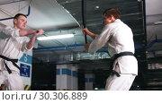 Купить «Two young men in kimono training kendo on a parking lot. Sword fight», видеоролик № 30306889, снято 8 июля 2020 г. (c) Константин Шишкин / Фотобанк Лори