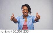 Купить «happy african american woman showing thumbs up», видеоролик № 30307233, снято 10 марта 2019 г. (c) Syda Productions / Фотобанк Лори