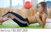 Купить «Young athletic woman laying on the yoga mat and looking at her abs», видеоролик № 30307269, снято 22 марта 2019 г. (c) Константин Шишкин / Фотобанк Лори