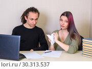 Купить «Молодой человек сидит задумчиво, девушка комкает документ в руках», фото № 30313537, снято 14 марта 2019 г. (c) Гетманец Инна / Фотобанк Лори