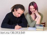 Купить «Молодая девушка , улыбаясь,  смотрит на то, что пишет подросток за столом», фото № 30313541, снято 14 марта 2019 г. (c) Гетманец Инна / Фотобанк Лори