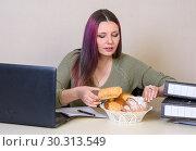 Молодая девушка за столом в офисе берет круасан из тарелки с выпечкой. Стоковое фото, фотограф Гетманец Инна / Фотобанк Лори