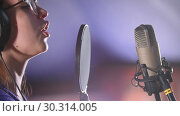 Купить «A young woman in glasses recording a song in the studio», видеоролик № 30314005, снято 23 марта 2019 г. (c) Константин Шишкин / Фотобанк Лори
