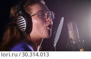 Купить «An emotional young woman in glasses recording a song in the studio», видеоролик № 30314013, снято 23 марта 2019 г. (c) Константин Шишкин / Фотобанк Лори