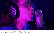 Купить «A young woman in glasses and headphones comes to the mic stand and starts singing. Purple neon lighting», видеоролик № 30314065, снято 23 марта 2019 г. (c) Константин Шишкин / Фотобанк Лори