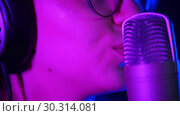 Купить «Emotional young woman singing in the studio. Purple neon lighting. Lips», видеоролик № 30314081, снято 4 июля 2020 г. (c) Константин Шишкин / Фотобанк Лори