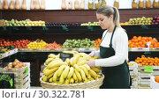 Купить «Portrait of young smiling saleswoman with yellow bananas in store», видеоролик № 30322781, снято 12 февраля 2019 г. (c) Яков Филимонов / Фотобанк Лори