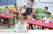 Купить «Portrait of smiling smart school children sitting with hands raised during lesson with female teacher in classroom», видеоролик № 30323025, снято 30 января 2019 г. (c) Яков Филимонов / Фотобанк Лори