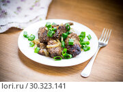 fried liver with onions in a plate on a wooden. Стоковое фото, фотограф Peredniankina / Фотобанк Лори