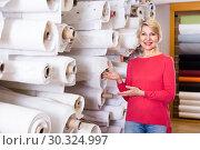 Купить «Mature female customer is showing bought home textiles», фото № 30324997, снято 15 февраля 2017 г. (c) Яков Филимонов / Фотобанк Лори
