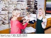 Купить «Woman seller displaying diverse fabrics», фото № 30325001, снято 15 февраля 2017 г. (c) Яков Филимонов / Фотобанк Лори