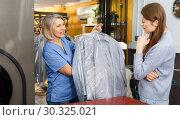 Купить «Worker giving woman her clean clothes», фото № 30325021, снято 22 января 2019 г. (c) Яков Филимонов / Фотобанк Лори