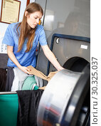 Купить «Woman in uniform taking out clothes from washing machine at laundry», фото № 30325037, снято 22 января 2019 г. (c) Яков Филимонов / Фотобанк Лори