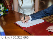 Купить «Жених ставит подпись в документах о заключение брака во Дворце бракосочетания», фото № 30325665, снято 26 июля 2018 г. (c) Алёшина Оксана / Фотобанк Лори