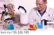 Купить «A young scientist conducts chemistry classes for a schoolgirl doing experiments with liquid nitrogen and dry ice in a chemical laboratory», видеоролик № 30326185, снято 17 марта 2019 г. (c) Алексей Кузнецов / Фотобанк Лори