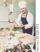 Купить «Smiling seller shows hands fish on counter», фото № 30326913, снято 27 октября 2016 г. (c) Яков Филимонов / Фотобанк Лори