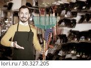 Купить «Seller displaying various items in garden equipment shop», фото № 30327205, снято 2 марта 2017 г. (c) Яков Филимонов / Фотобанк Лори