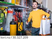Купить «Positive guy deciding on best garden sprayer», фото № 30327209, снято 2 марта 2017 г. (c) Яков Филимонов / Фотобанк Лори