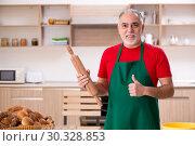 Купить «Old male baker working in the kitchen», фото № 30328853, снято 24 декабря 2018 г. (c) Elnur / Фотобанк Лори