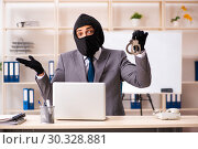 Купить «Male gangster stealing information from the office», фото № 30328881, снято 20 декабря 2018 г. (c) Elnur / Фотобанк Лори