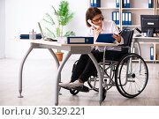 Купить «Female employee in wheel-chair at the office», фото № 30329221, снято 4 декабря 2018 г. (c) Elnur / Фотобанк Лори