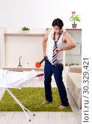Купить «Young man ironing in the bedroom», фото № 30329421, снято 29 ноября 2018 г. (c) Elnur / Фотобанк Лори