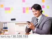 Купить «Young handsome employee working in the office», фото № 30330193, снято 16 октября 2018 г. (c) Elnur / Фотобанк Лори